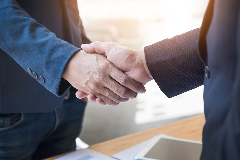 Two confident business man shaking hands during a meeting in the
